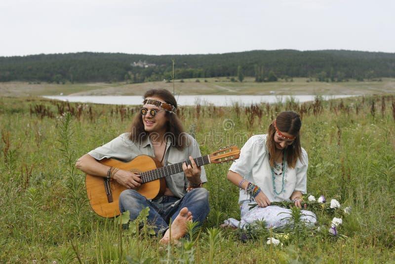 Los hombres del hippie juegan en la guitarra y la mujer hace una guirnalda foto de archivo libre de regalías