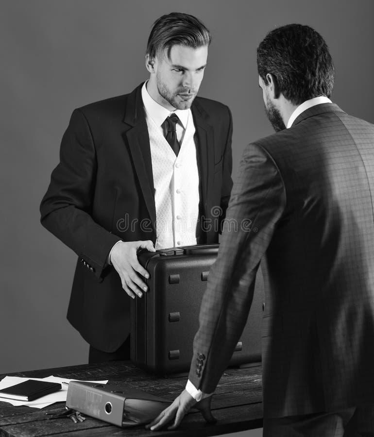 Los hombres en traje o los hombres de negocios se encuentran para la entrega del negro fotos de archivo