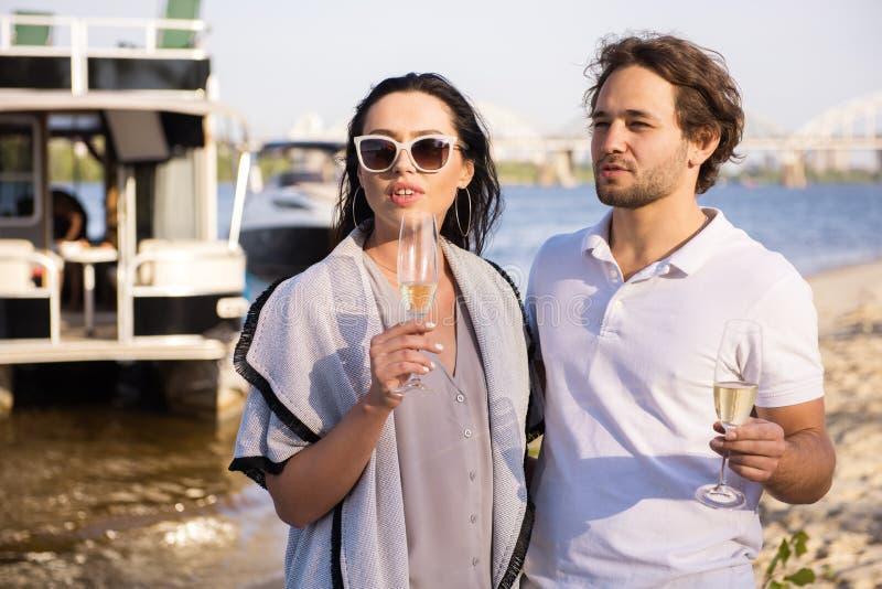 Los hombres están bebiendo el champán con sus pares en la playa foto de archivo