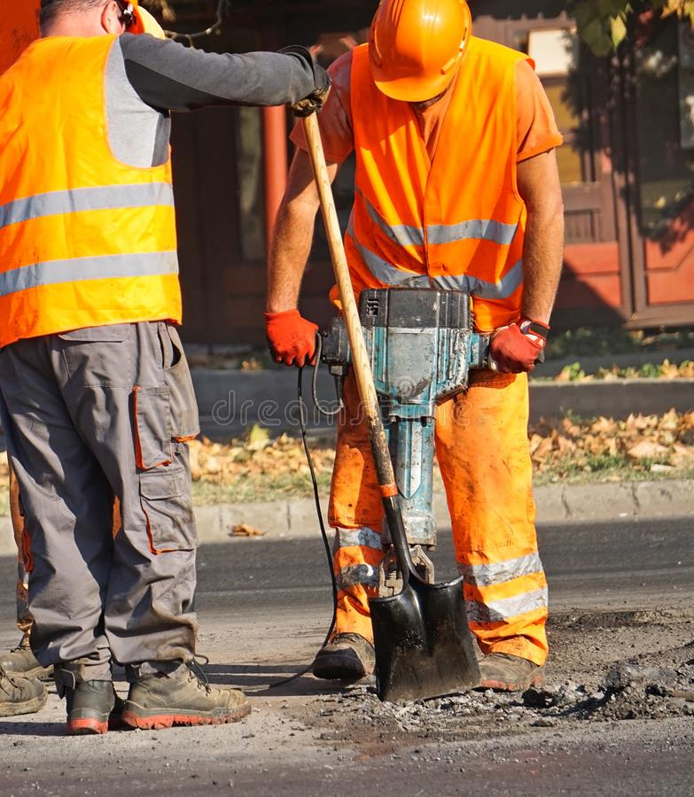 Los hombres están trabajando en la construcción de carreteras fotos de archivo