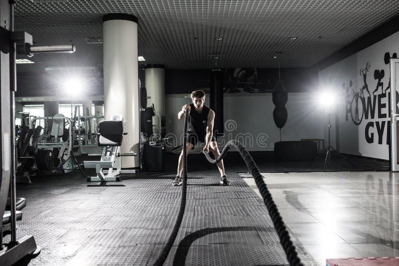Los hombres fuertes con la cuerda de la batalla luchan cuerdas ejercitan en el gimnasio de la aptitud Crossfit imágenes de archivo libres de regalías