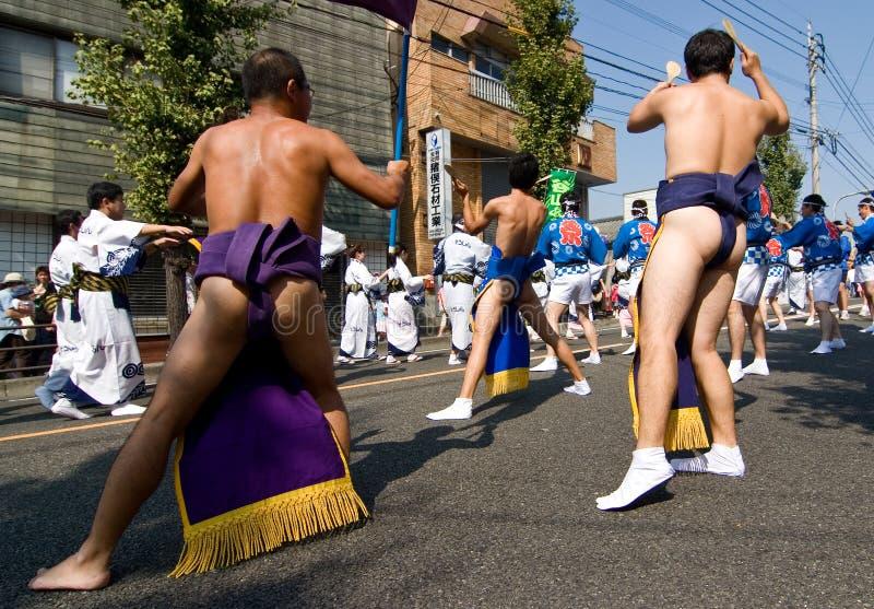 Los hombres japoneses en correas del sumo bailan en un desfile foto de archivo