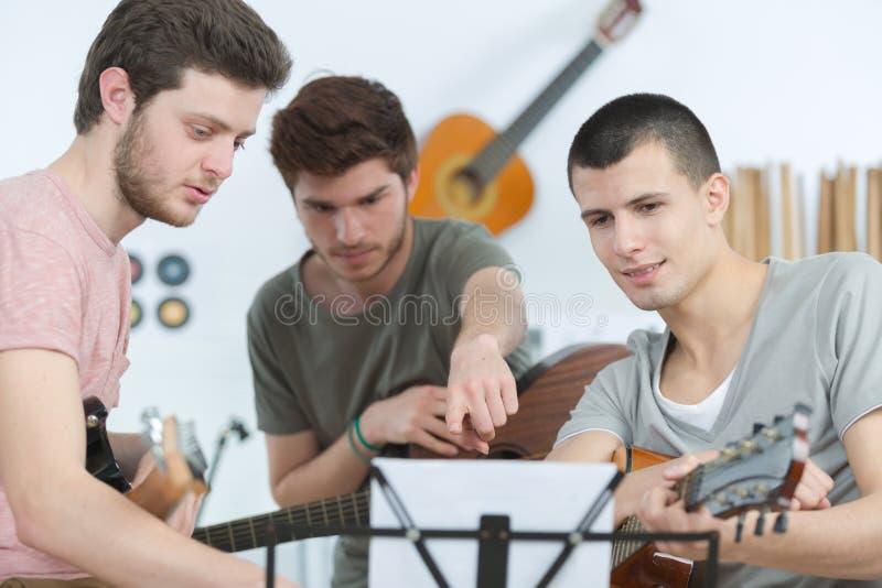 Los hombres jovenes dan tocar la guitarra en casa foto de archivo