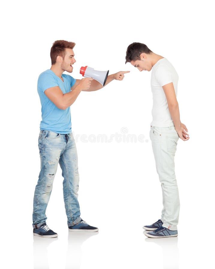 Los hombres jovenes gritan a su amigo a través de un megáfono fotografía de archivo libre de regalías