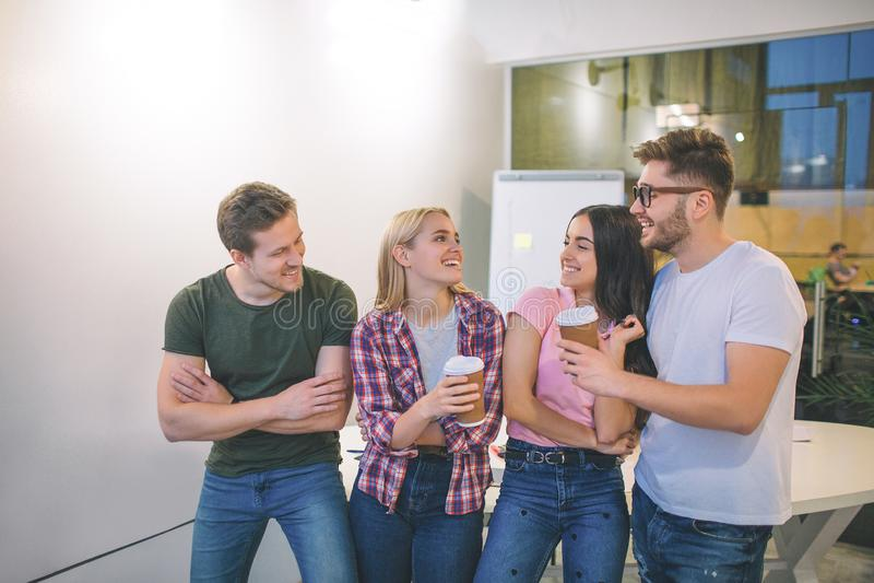 Los hombres jovenes y las mujeres alegres y positivos se unen Miran uno a y risa La gente positiva sostiene las tazas fotos de archivo libres de regalías