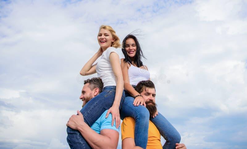 Los hombres llevan a novias en hombros Vacaciones y diversi?n de verano Pares fecha doble Invitaci?n de otros pares que se unan a imagen de archivo
