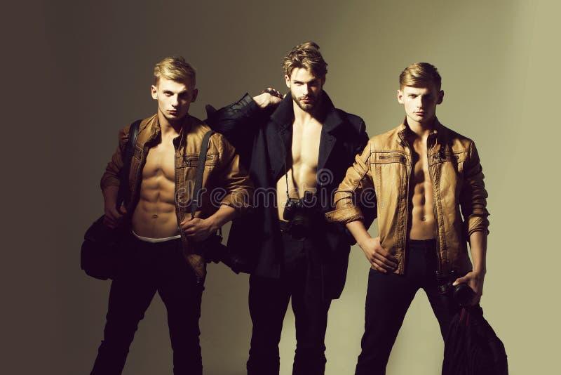 Los hombres musculares del fotógrafo con el cuerpo atractivo sostienen la cámara profesional de la foto fotos de archivo