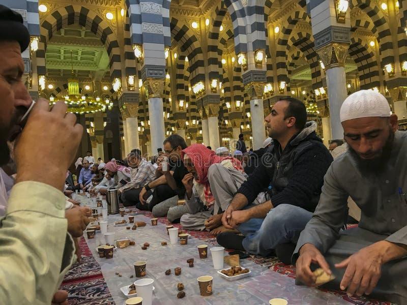 Los hombres musulmanes no identificados se rompen rápidamente en el amanecer dentro de la mezquita de Nabawi en Medina, la Arabia imagen de archivo