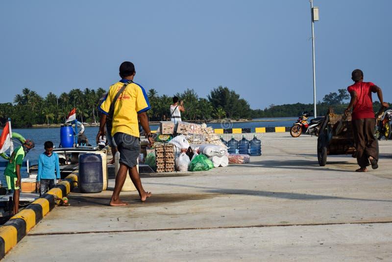 Los hombres negocian en una amplia variedad de ventas en los muelles de Sebesi en Lampung, en Indonesia imagen de archivo