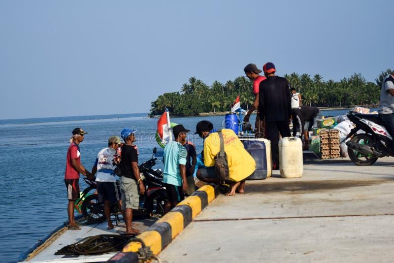 Los hombres negocian en una amplia variedad de ventas en los muelles de Sebesi en Lampung, en Indonesia imagenes de archivo