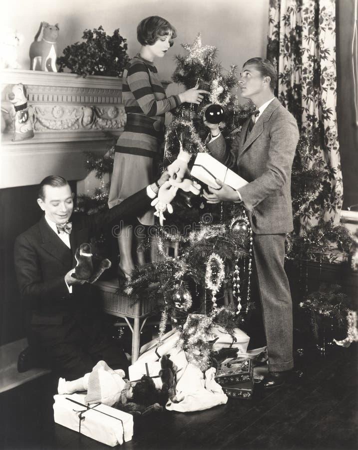 Los hombres que ayudan a la mujer adornan el árbol de navidad en casa fotos de archivo libres de regalías
