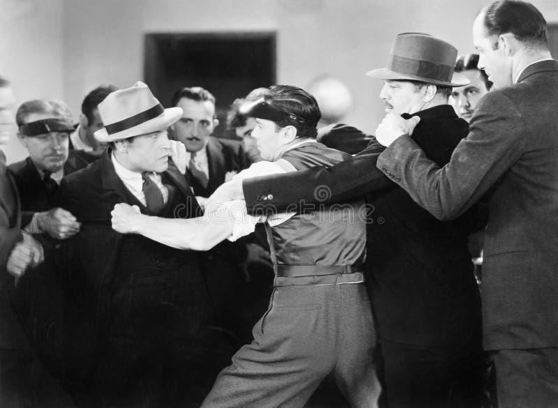 Los hombres que luchan una parte posterior del hombre que esté intentando perforar a otro hombre (todas las personas representada fotografía de archivo libre de regalías
