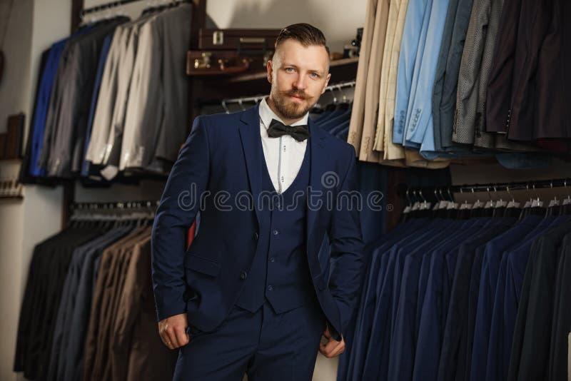 Los hombres se adaptan a perfecto al detalle pasado Hombre que presenta en traje marrón imagen de archivo libre de regalías
