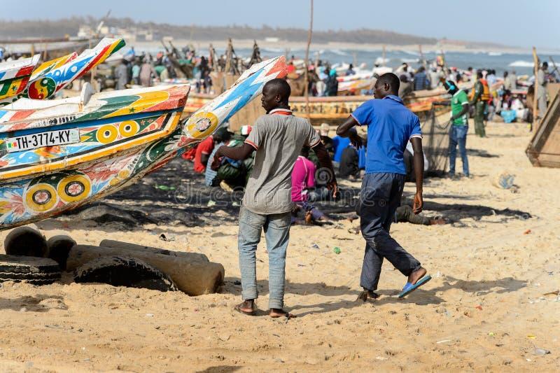 Los hombres senegaleses no identificados caminan en la costa del O atlántico imagen de archivo