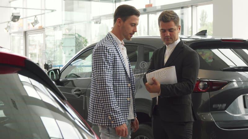 Los hombres serios firman un contrato de compra del coche foto de archivo