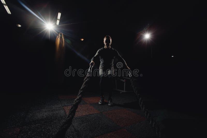 Los hombres siluetean con la cuerda de la batalla en gimnasio de entrenamiento funcional de la aptitud fotografía de archivo libre de regalías