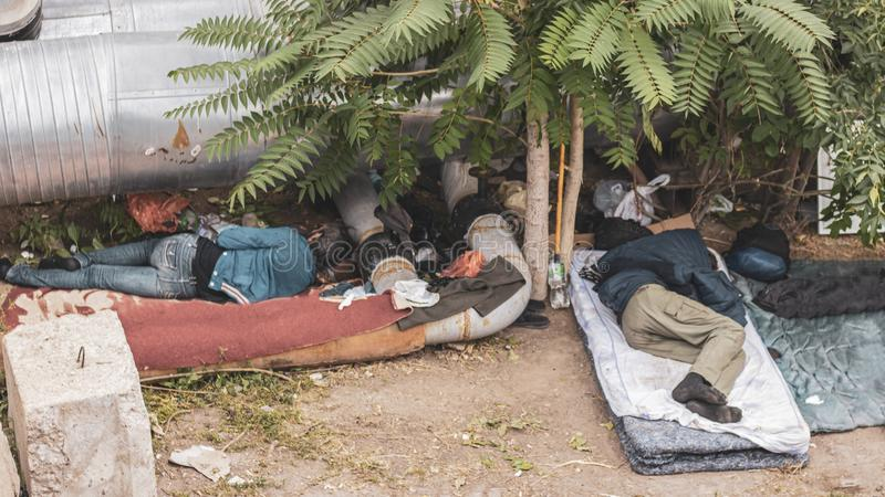 Los hombres sin hogar sucios y hambrientos duermen debajo de una palmera y de los tubos debajo de un puente en la ciudad fotos de archivo libres de regalías