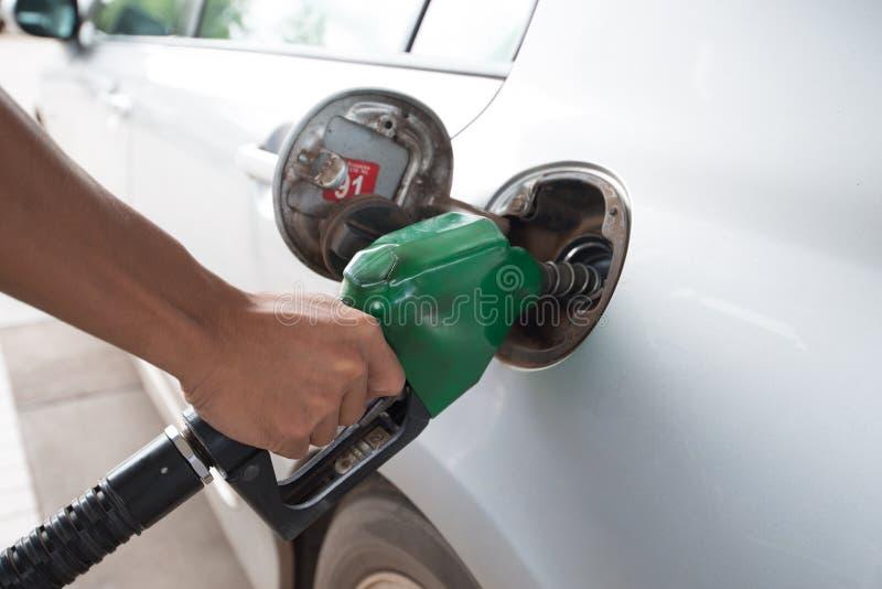 Los hombres sostienen el surtidor de gasolina para añadir el combustible en coche foto de archivo