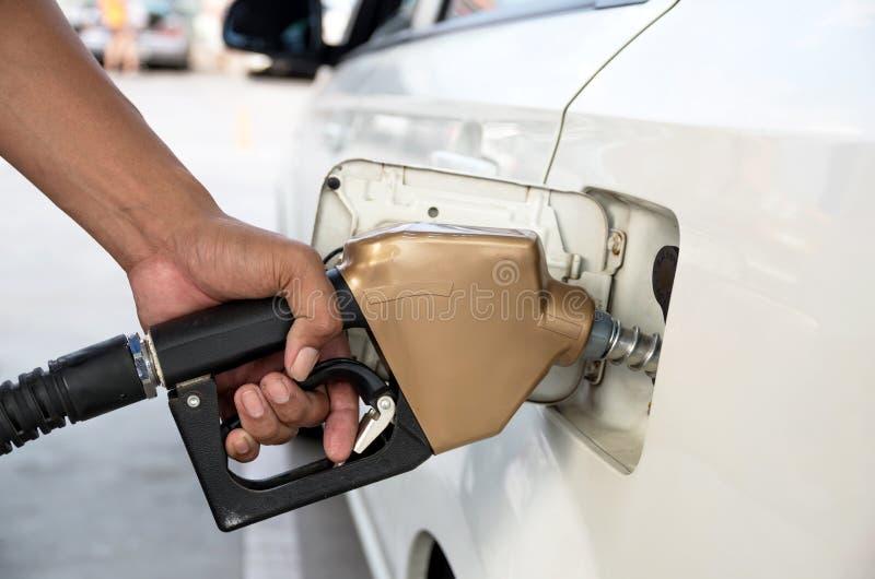 Los hombres sostienen el surtidor de gasolina para añadir el combustible en coche en la estación de servicio imagenes de archivo