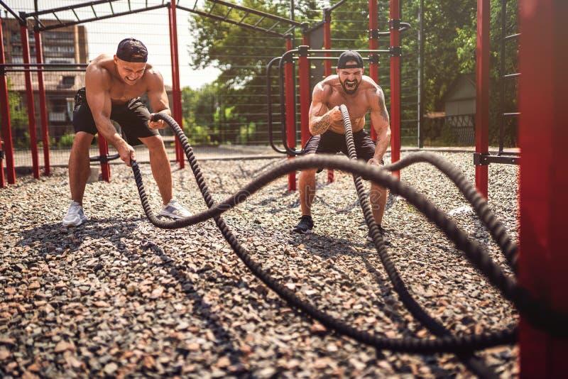 Los hombres trabajan difícilmente con la cuerda en la yarda del gimnasio de la calle Fuerza y motivaci?n Entrenamiento al aire li foto de archivo