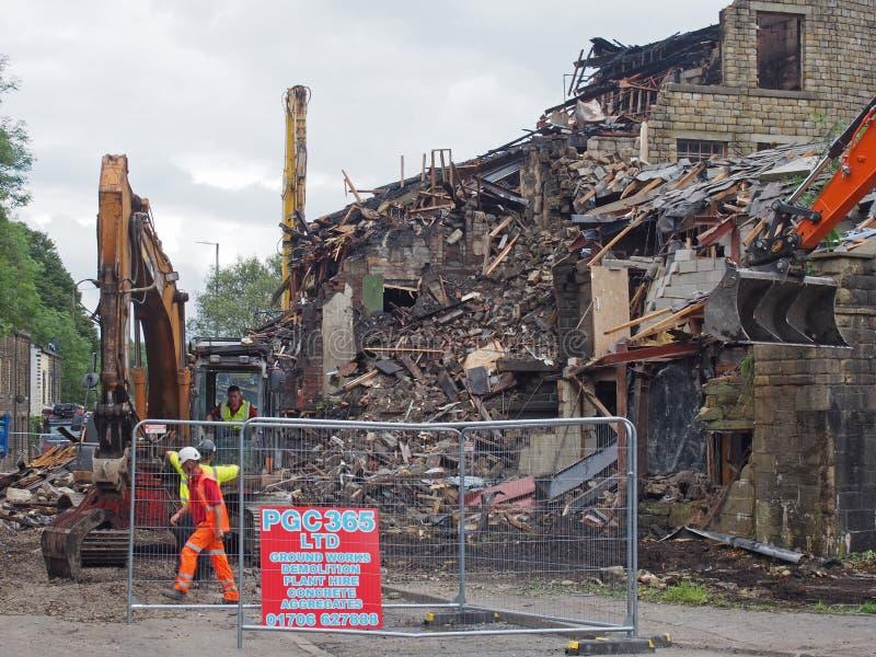 Los hombres y la maquinaria de construcción en la demolición del edificio del molino de los walkeys adentro hebden el puente desp imagen de archivo