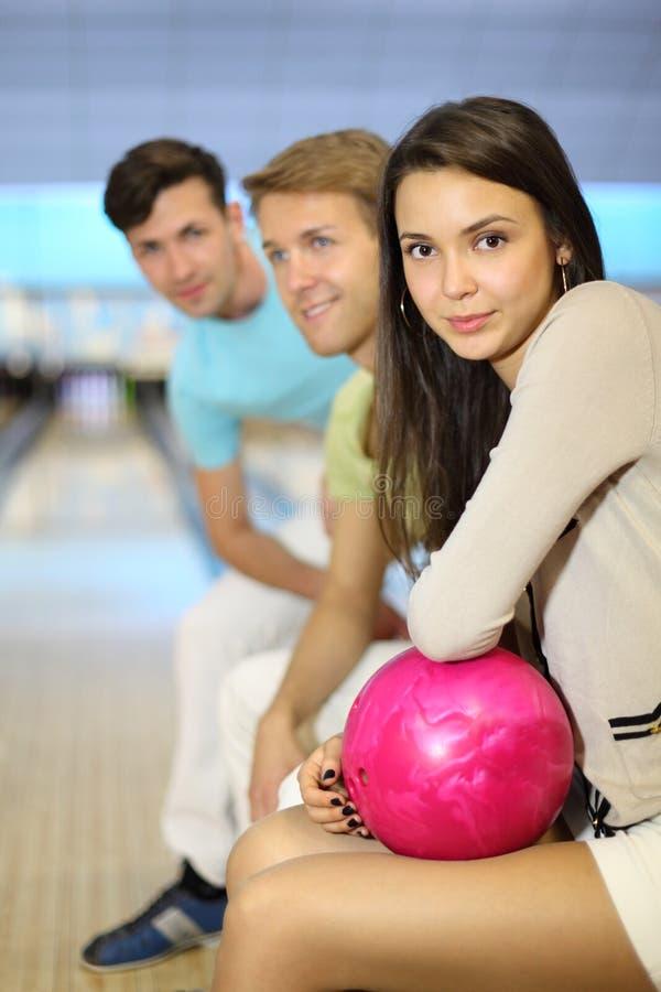 Los hombres y la mujer se sientan en club del bowling imagenes de archivo