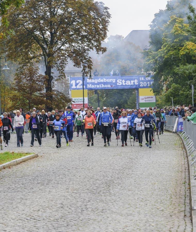 Los hombres y las mujeres que caminan del nordic con sonrisas se divierten el día de fiesta, maratón en Alemania, Magdeburgo, okt imagen de archivo