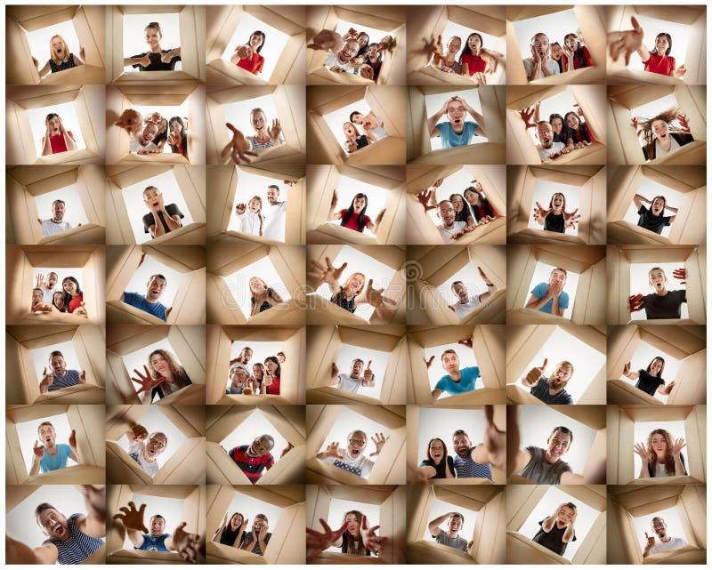 Los hombres y las mujeres que desempaquetan y que abren la caja del cartón y que miran dentro imagen de archivo