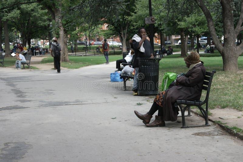Los hombres y las mujeres sin hogar en una ciudad parquean imagen de archivo