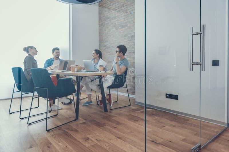 Los hombres y las mujeres sonrientes están hablando en sala de reunión fotografía de archivo
