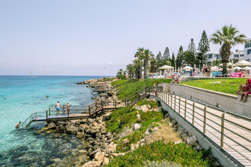 Los hoteles y la playa en la higuera aúllan en Protaras chipre fotos de archivo
