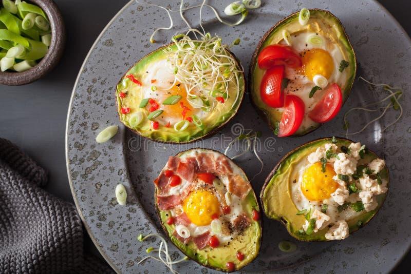 Los huevos cocieron en aguacate con el spr del tocino, del queso, del tomate y de la alfalfa fotografía de archivo