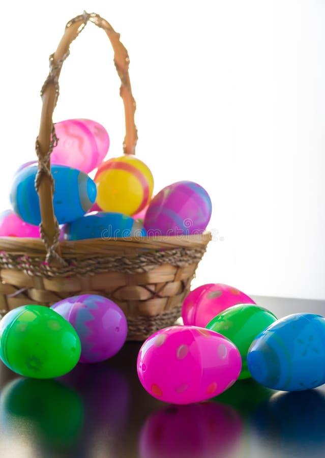 Los huevos de Pascua adornados están en una tabla y en una cesta fotos de archivo