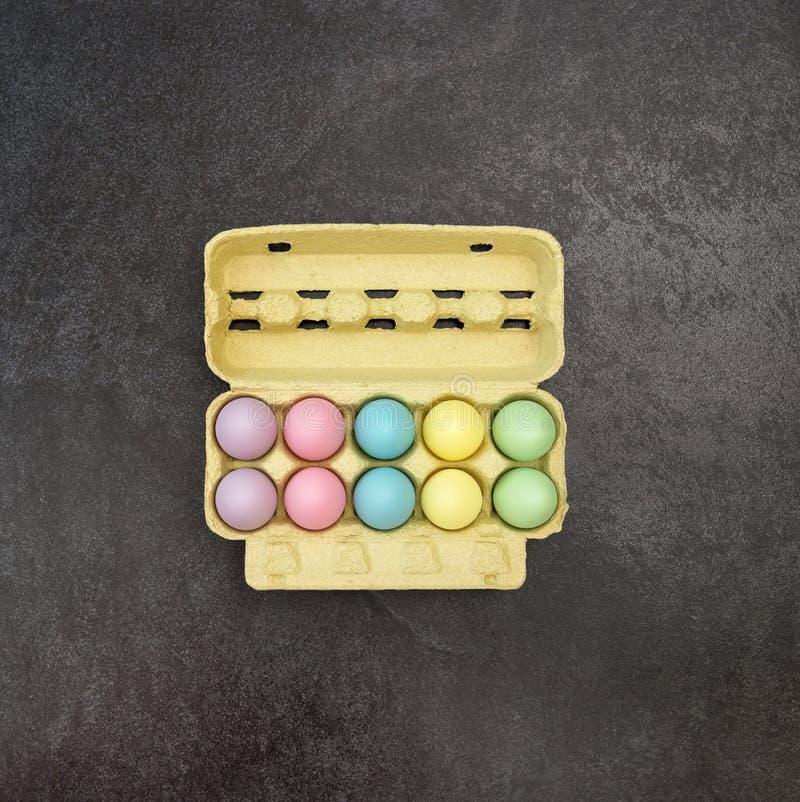 Los huevos de Pascua colorearon el fondo del negro del cartón de huevos foto de archivo