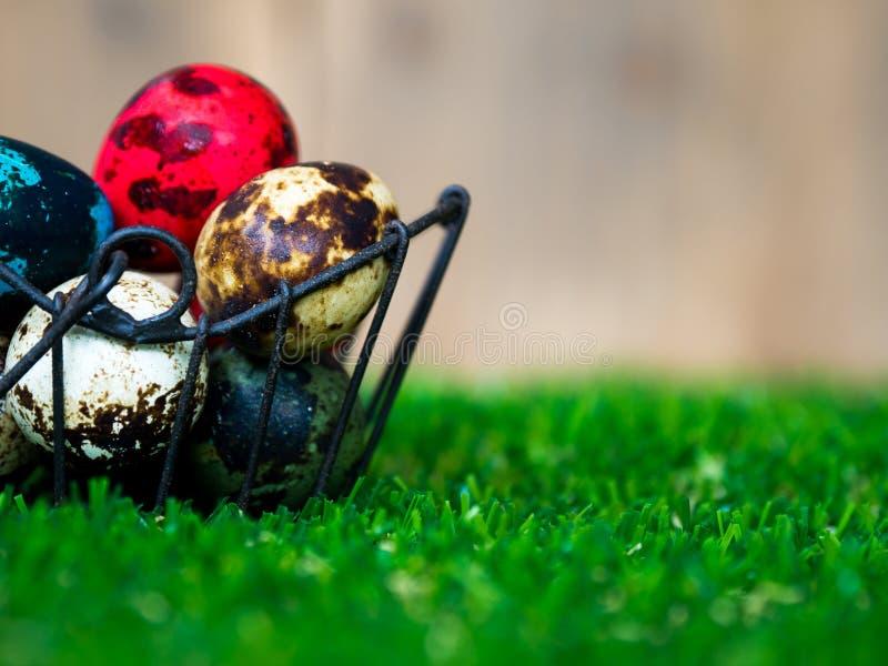 Los huevos de Pascua coloridos están en la cesta Colocado en hierba verde Tenga un conejo lindo en la parte posterior La parte po fotos de archivo