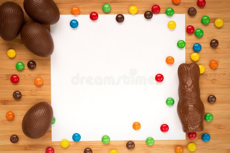 Los huevos de Pascua del chocolate, gragea del caramelo, conejito de pascua en una luz cortejan imagenes de archivo