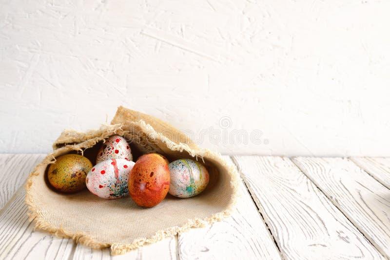 Los huevos de Pascua envolvieron en tela de la lona en fondo ligero imagen de archivo libre de regalías