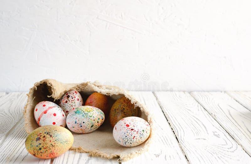 Los huevos de Pascua envolvieron en tela de la lona en fondo ligero imágenes de archivo libres de regalías