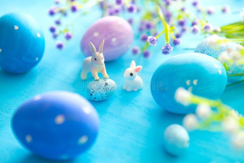 Los huevos de Pascua hermosos con los conejos juegan y las flores en el fondo de madera azul, primer Concepto del día de fiesta d fotografía de archivo libre de regalías
