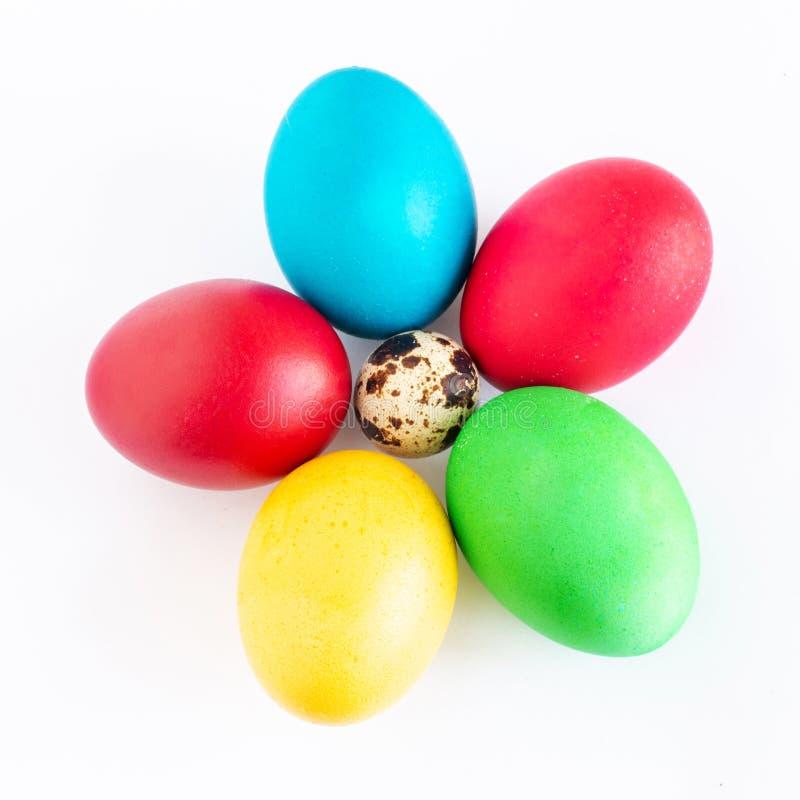 Los huevos de Pascua multicolores mienten en un fondo blanco Huevo amarillo, rojo, verde y azul doblado bajo la forma de flor fotografía de archivo