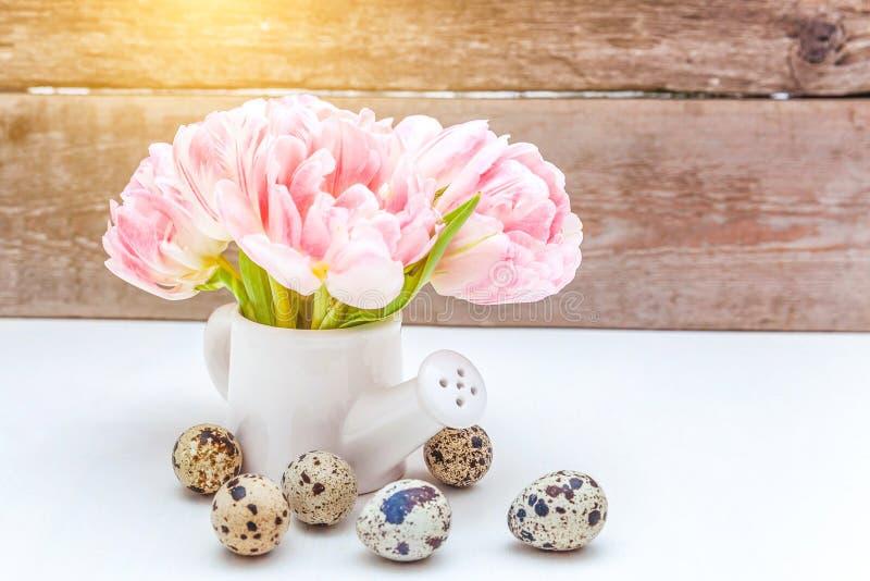 Los huevos de Pascua pican el ramo fresco de las flores del tulipán y el pequeño florero de la regadera del juguete en fondo de m fotos de archivo
