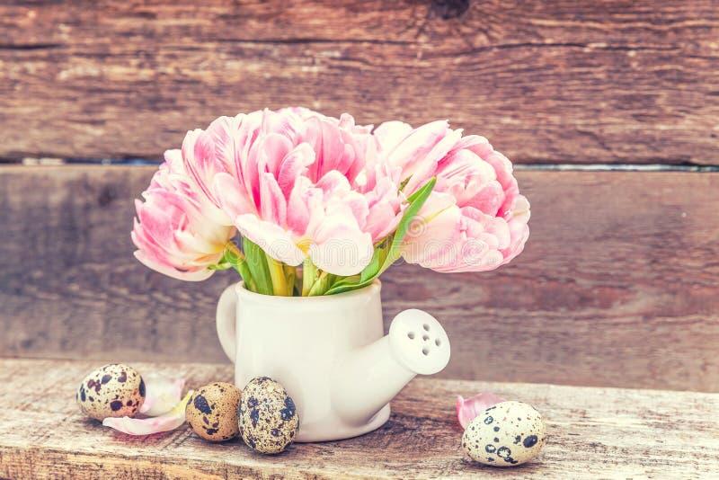 Los huevos de Pascua pican el ramo fresco de las flores del tulipán y el pequeño florero de la regadera del juguete en fondo de m imagen de archivo