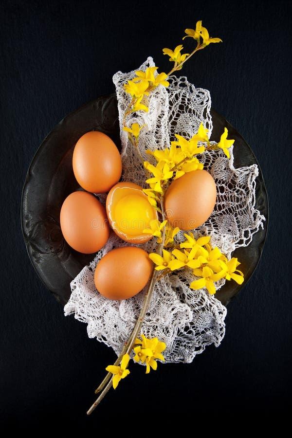 Los huevos del ` s de la gallina de Brown adornan con las flores amarillas en la placa antigua, fotografía rústica de la comida foto de archivo libre de regalías