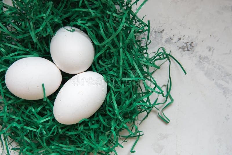 Los huevos en un Libro Verde jerarquizan tres huevos blancos fotos de archivo