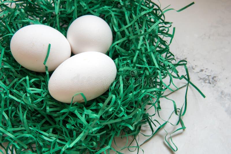Los huevos en un Libro Verde jerarquizan tres huevos blancos foto de archivo libre de regalías