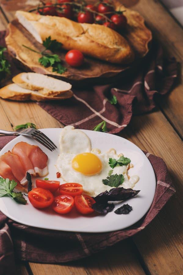 Los huevos fritos con el tomate, la albahaca y el prosciutto, tabla fijaron para el desayuno acogedor imagen de archivo