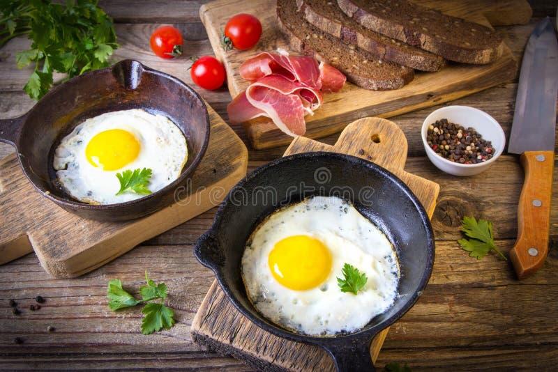 Los huevos fritos en dos pequeños sartenes se sirven con pan hecho en casa con las semillas, el jamón, los tomates y el perejil imágenes de archivo libres de regalías
