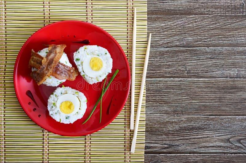 Los huevos hervidos envolvieron en arroz con las cebollas verdes con las rebanadas de tocino en una placa roja fotografía de archivo libre de regalías