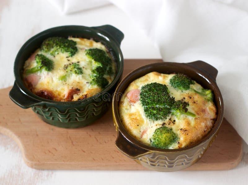 Los huevos revueltos Baked con bróculi, las salchichas y el queso sirvieron con las rebanadas de pan Estilo rústico imagenes de archivo