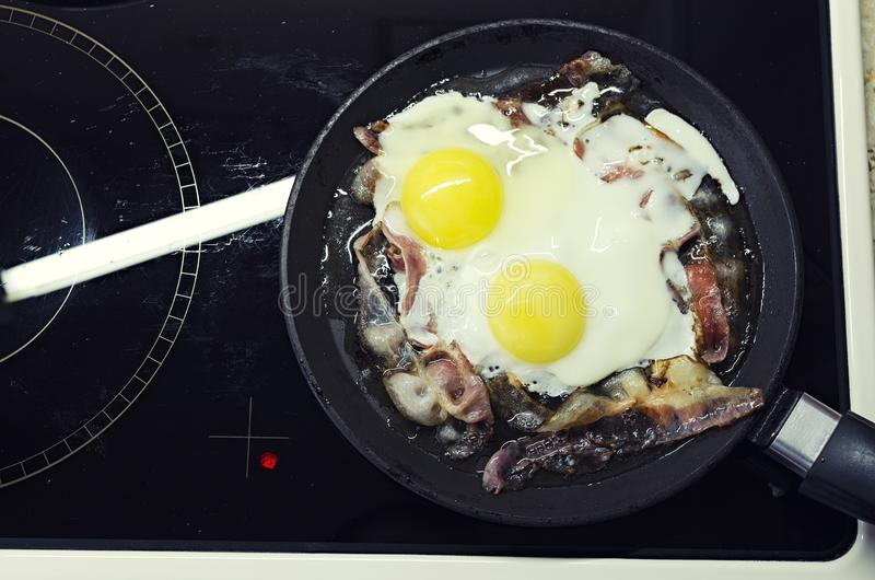 Los huevos revueltos que cocinaban en un sartén, cocinando en una estufa de cerámica, los huevos revueltos con el tocino, visión  imagenes de archivo